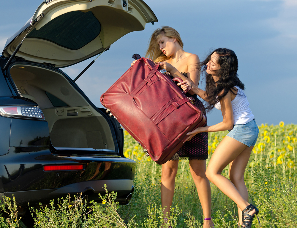 Two woman trying to put a heavy piece of luggage into the trunk of a car.