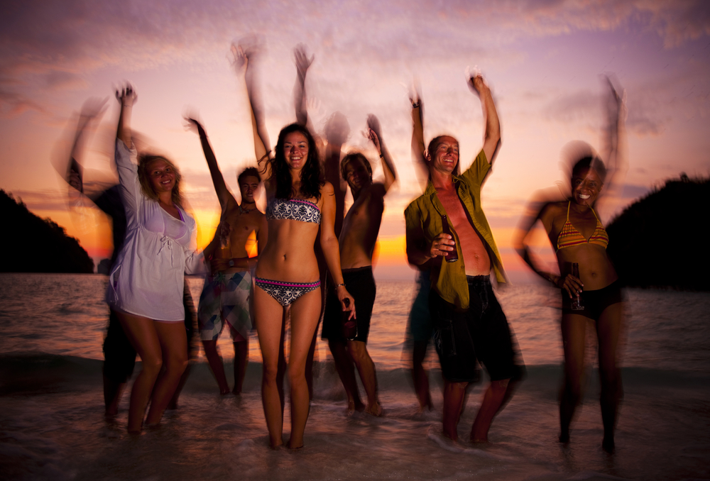 Group of friends having a blast while dancing on beach to celebrate spring breaks.