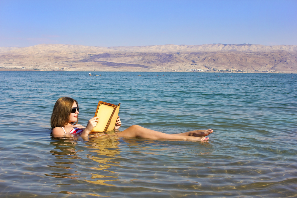 Woman reading a book while floating in the Dead Sea, Israel.