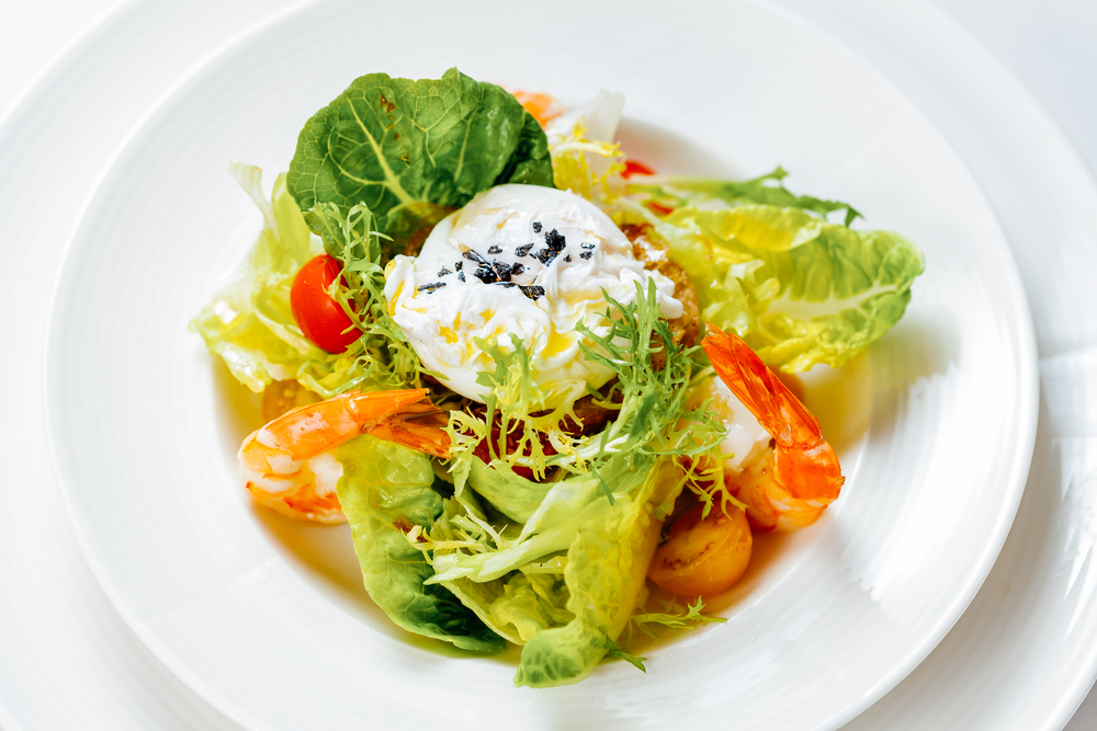 Salad with poached egg and shrimp.