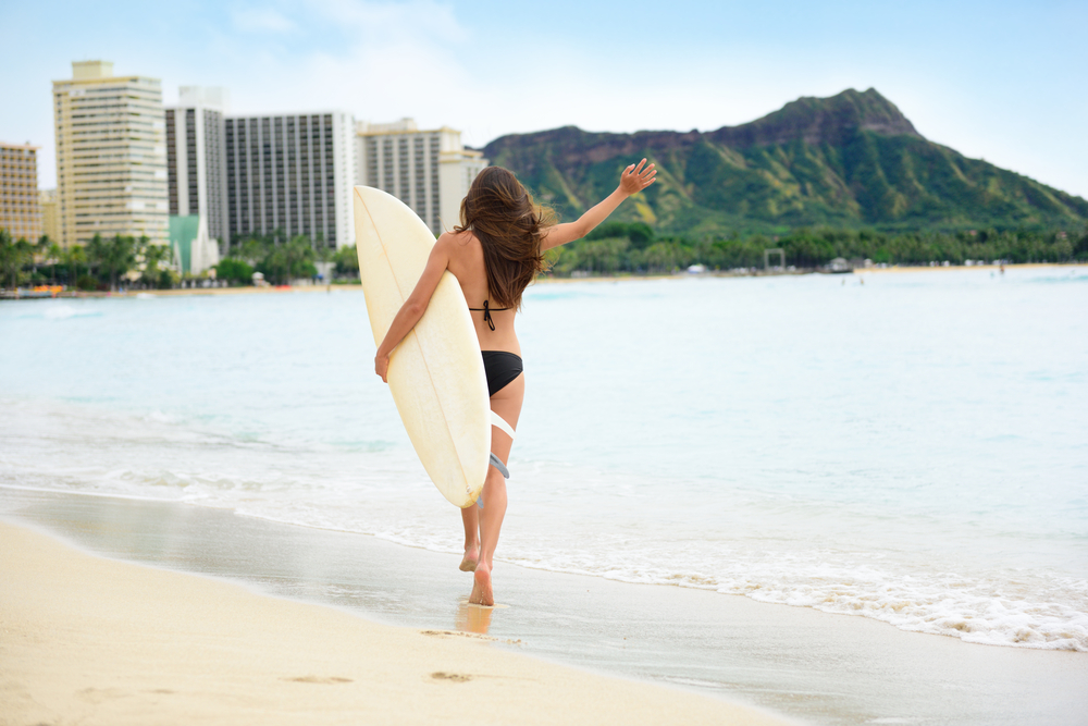 Woman going to surf in Waikiki Beach