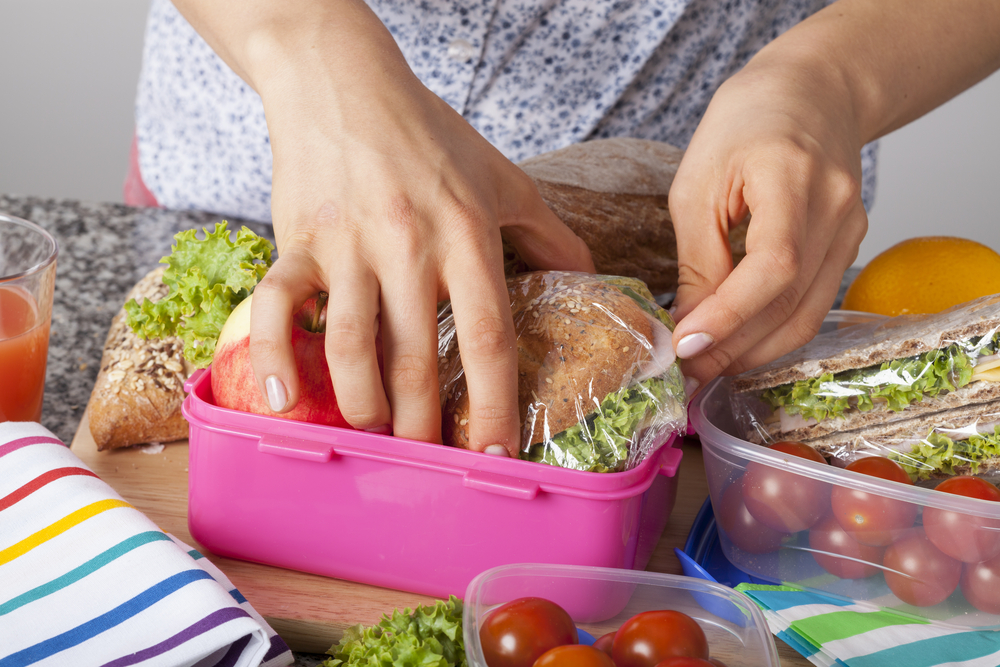womans hands packing lunch
