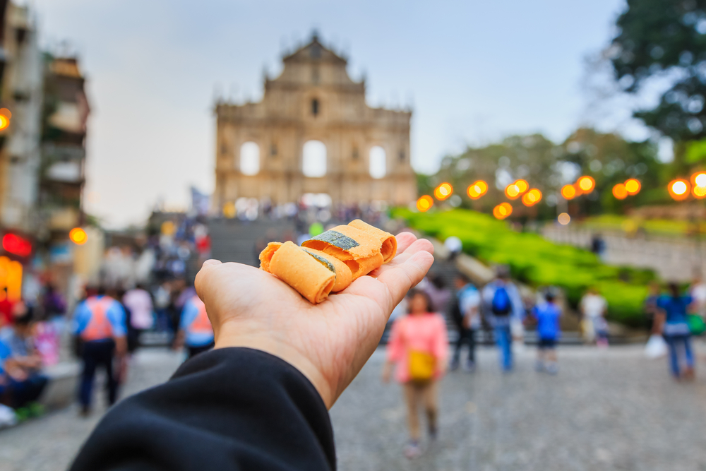 Man holding up snacks with Macau as background